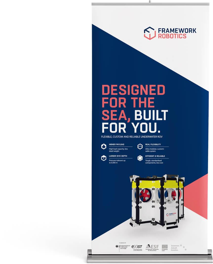 Das Bild zeigt eine Simulation eines möglichen Rollup Banners für den Kunden FRAMEWORK Robotics. Das Poster beinhaltet alle wesentlichen Kommunikations- und Designelemente des Corporate Designs sowie eine Produktabbildung des vom Kunden entwickelten ROV Unterwasserroboters.